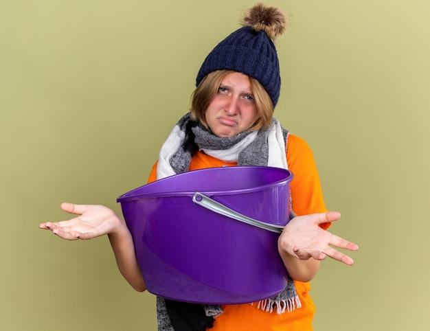 Ongezonde jonge vrouw die hoed met sjaal om haar nek draagt, zich onwel voelt en lijdt aan misselijkheid die een bassin vasthoudt en verward schouders ophaalt die over een groene muur staan