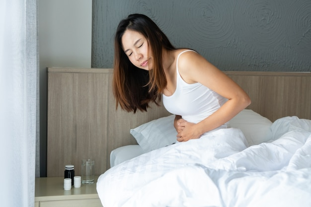 Ongezonde jonge vrouw die op bed zit en buik vasthoudt, zich ongemakkelijk voelt en lijdt aan buikpijn, voedselvergiftiging, ongesteld. gezondheidsprobleem concept