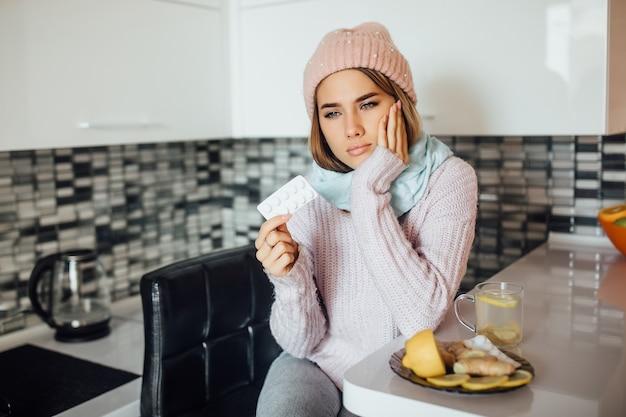 Ongezonde jonge vrouw die pil bij de hand houdt terwijl ze griep heeft?