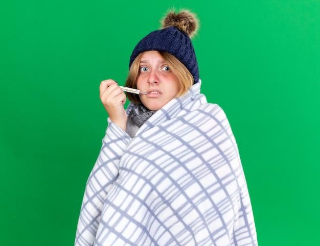 Ongezonde jonge vrouw gewikkeld in een deken met een hoed die haar lichaamstemperatuur meet met behulp van een thermometer die lijdt aan griep en koorts heeft en er bezorgd uitziet terwijl ze over de groene muur staat