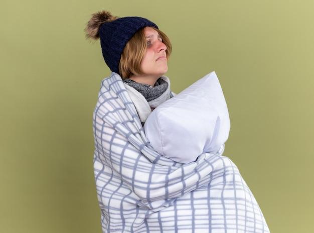 Ongezonde jonge vrouw gewikkeld in een deken met een hoed met een kussen die lijdt aan griep en zich ziek voelt en opzij kijkt met een droevige uitdrukking die over de groene muur staat