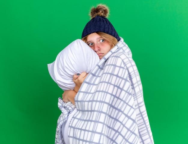 Ongezonde jonge vrouw gewikkeld in een deken met een hoed met een kussen die lijdt aan verkoudheid en griep en zich ziek voelt terwijl ze over de groene muur staat