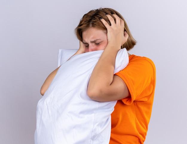 Ongezonde jonge vrouw in een oranje t-shirt met een kussen die zich ziek voelt en lijdt aan griep met koorts en sterke hoofdpijn die over een witte muur staat