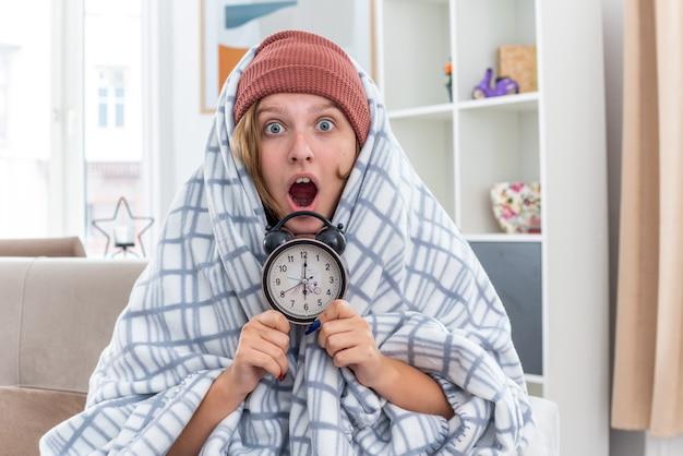 Ongezonde jonge vrouw in hoed gewikkeld in deken die lijdt aan verkoudheid en griep met wekker die er verbaasd en verbaasd uitziet terwijl ze op de bank zit in een lichte woonkamer