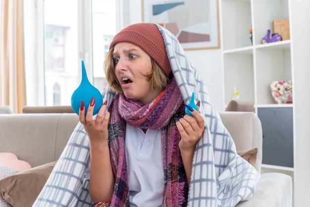Ongezonde jonge vrouw in hoed gewikkeld in deken onwel voelen en ziek bedrijf klysma's op zoek verward zittend op de bank in lichte woonkamer