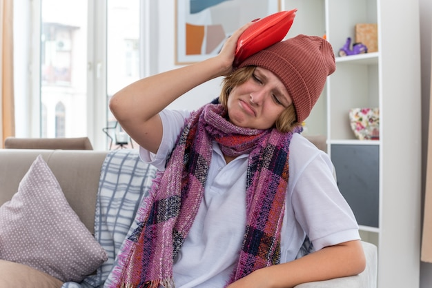 Ongezonde jonge vrouw in hoed met warme sjaal om nek voelt zich onwel en ziek en lijdt aan verkoudheid en griep met een warmwaterkruik op haar hoofd en ziet er bezorgd uit zittend op de bank in een lichte woonkamer