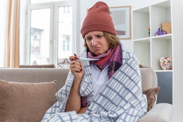 Ongezonde jonge vrouw in muts met warme sjaal om nek met thermometer die haar temperatuur controleert, zich onwel voelt en lijdt aan verkoudheid en griep, bezorgd zittend op de bank in een lichte woonkamer