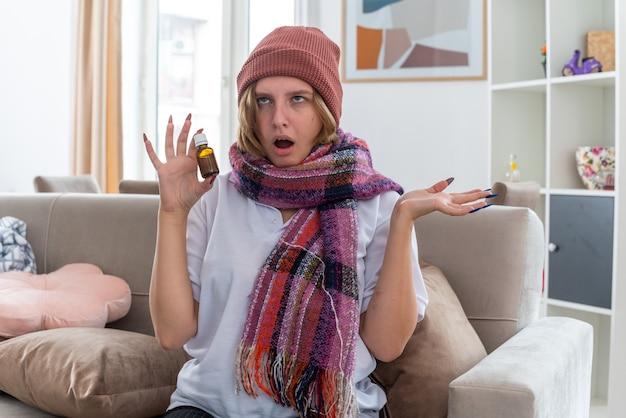 Ongezonde jonge vrouw in muts met warme sjaal om nek zich onwel en ziek voelen die lijden aan verkoudheid en griep houden van medicijnfles gestrest en geïrriteerd zittend op de bank in lichte woonkamer