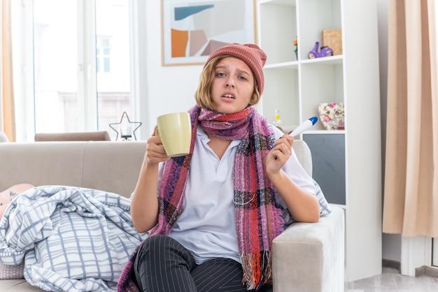 Ongezonde jonge vrouw in muts met warme sjaal om nek zich onwel en ziek voelen die lijdt aan verkoudheid en griep met thermometer en kopje bezorgd en verdrietig zittend op de bank in lichte woonkamer