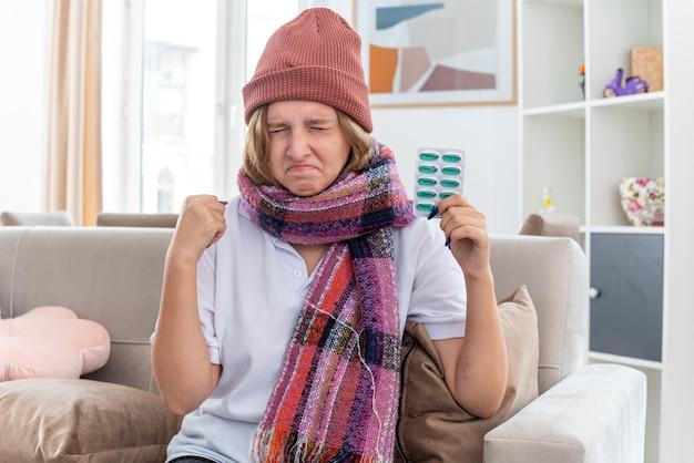 Ongezonde jonge vrouw in muts met warme sjaal om nek, zich onwel en ziek voelen en lijden aan verkoudheid en griep met pillen met gebalde vuist ogen dicht zittend op de bank in lichte woonkamer