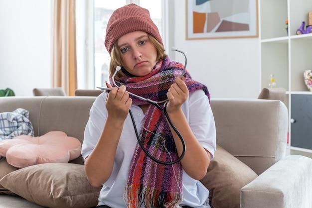 Ongezonde jonge vrouw in muts met warme sjaal om nek zich onwel en ziek voelen, lijden aan verkoudheid en griep luisteren naar haar pols met behulp van stethoscoop op zoek bezorgd zittend op de bank in lichte woonkamer