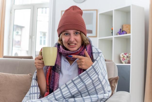 Ongezonde jonge vrouw in muts met warme sjaal rond nek hete thee drinken om beter lijden aan verkoudheid en griep zittend op de bank in lichte woonkamer