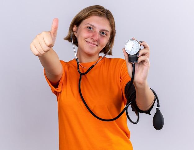 Ongezonde jonge vrouw in oranje t-shirt bloeddruk meten met behulp van tonometer met glimlach op gezicht duimen opdagen staande over witte muur