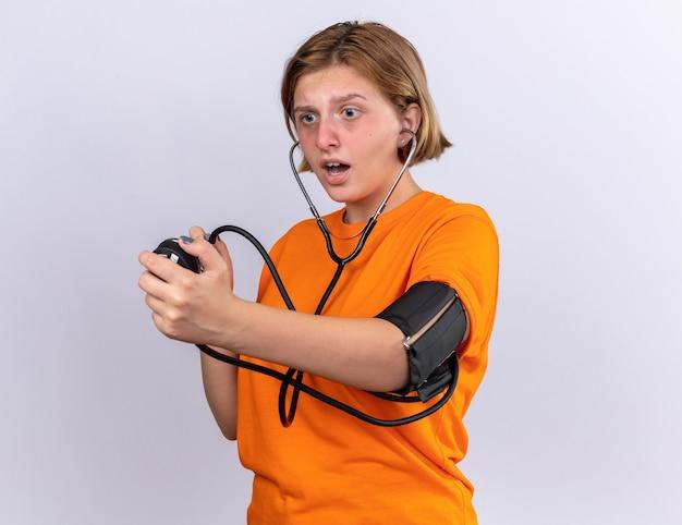 Ongezonde jonge vrouw in oranje t-shirt die bloeddruk meet met behulp van tonometer die zich zorgen maakt