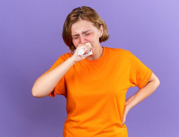 Ongezonde jonge vrouw in oranje t-shirt die vreselijk hoest in de vuist die lijdt aan een virus dat over de paarse muur staat