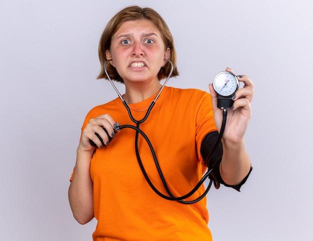 Ongezonde jonge vrouw in oranje t-shirt die zich onwel voelt bloeddruk meten met behulp van tonometer die bezorgd en teleurgesteld over de witte muur staat