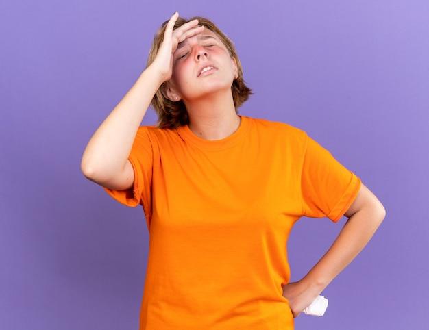 Ongezonde jonge vrouw in oranje t-shirt die zich onwel voelt en haar voorhoofd aanraakt terwijl ze zich duizelig voelt met griep die over een paarse muur staat