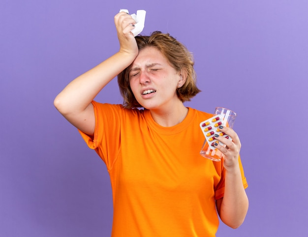 Ongezonde jonge vrouw in oranje t-shirt die zich onwel voelt met glas water en pillen die haar voorhoofd aanraken voor ziekte en koorts griep en verkoudheidsvirus ziek staande over paarse muur