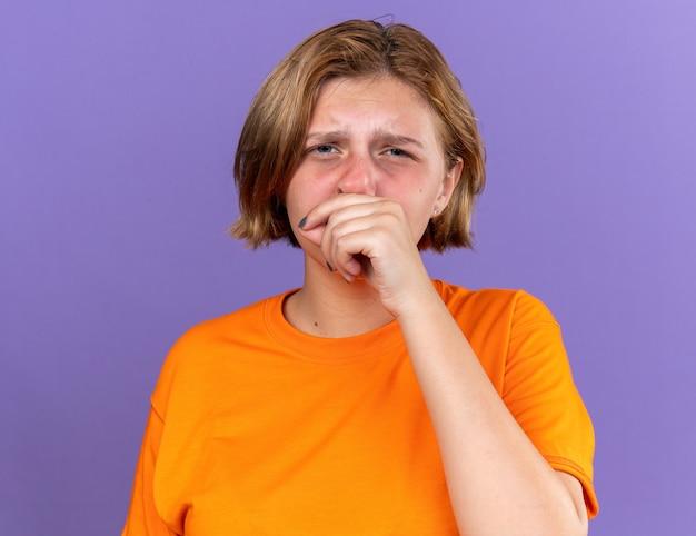 Ongezonde jonge vrouw in oranje t-shirt die zich vreselijk voelt als ze haar neus afveegt met koorts die verkouden is en over een paarse muur staat