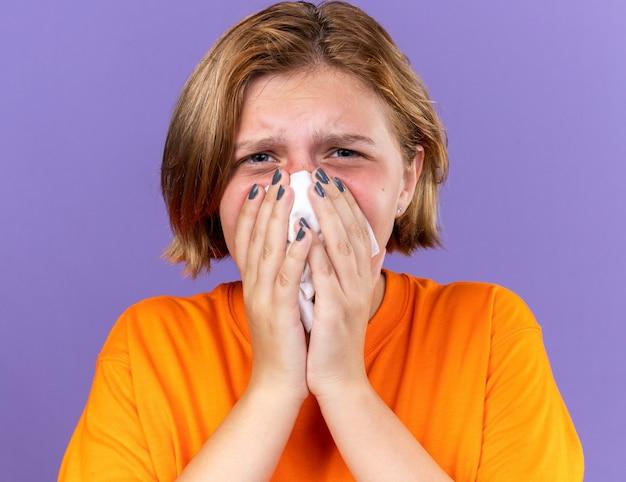 Ongezonde jonge vrouw in oranje t-shirt die zich vreselijk voelt blazende loopneus betrapt op koud niezen in weefsel dat over paarse muur staat