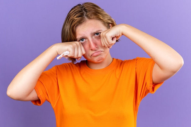 Ongezonde jonge vrouw in oranje t-shirt die zich vreselijk voelt met weefsel dat lijdt aan een loopneus, koud huilt, hard wrijvende ogen die over een paarse muur staan