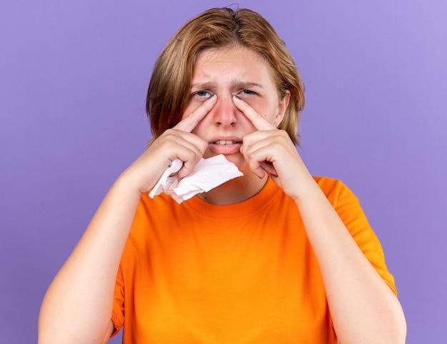 Ongezonde jonge vrouw in oranje t-shirt die zich vreselijk voelt met weefsel dat lijdt aan een loopneus, verkouden is