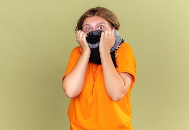 Ongezonde jonge vrouw in oranje t-shirt met gezichtsbeschermend masker met warme sjaal om nek en gezicht, zich onwel voelen lijdend aan kou en bezorgd over groene muur staan
