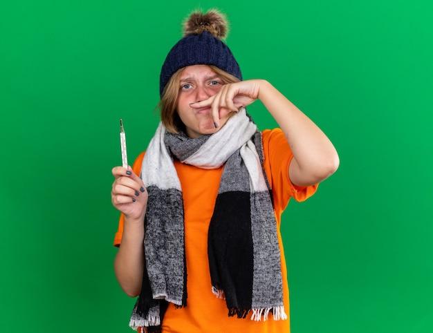 Ongezonde jonge vrouw in oranje t-shirt met hoed en warme sjaal om de nek die zich verschrikkelijk voelt met een thermometer met koorts die lijdt aan een loopneus die over de groene muur staat