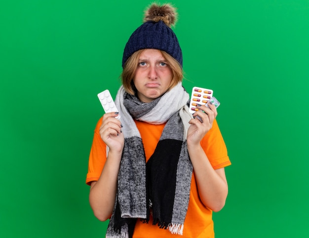Ongezonde jonge vrouw in oranje t-shirt met hoed en warme sjaal om de nek die zich vreselijk voelt met pillen die lijden aan een virus dat over de groene muur staat