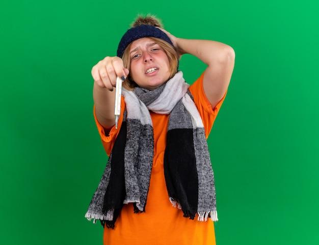 Ongezonde jonge vrouw in oranje t-shirt met hoed en warme sjaal om nek voelt zich verschrikkelijk met thermometer met koorts die lijdt aan griep