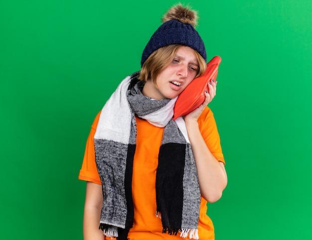 Ongezonde jonge vrouw in oranje t-shirt met hoed en warme sjaal om nek voelt zich verschrikkelijk met warmwaterkruik die lijdt aan verkoudheid en griep die over groene muur staat