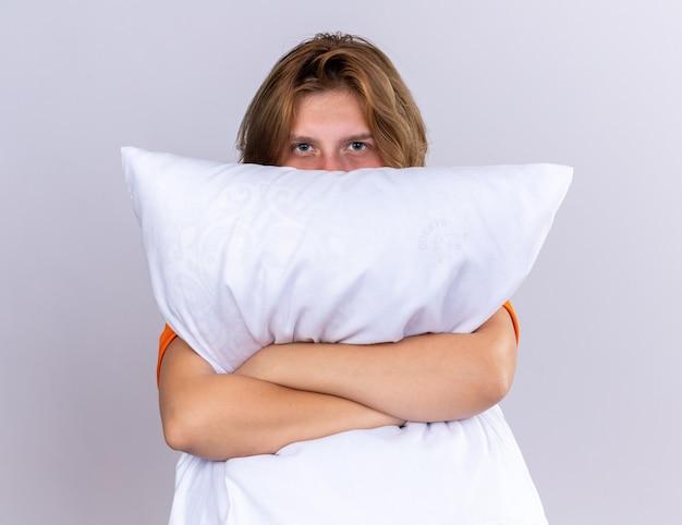 Ongezonde jonge vrouw in oranje t-shirt met kussen die zich onwel voelt en haar gezicht bedekt terwijl ze over kussen gluurt dat over een witte muur staat