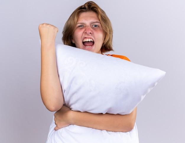 Ongezonde jonge vrouw in oranje t-shirt met kussen die zich onwel voelt gluren over kussen schreeuwend met agressieve uitdrukking die haar vuist over witte muur laat zien
