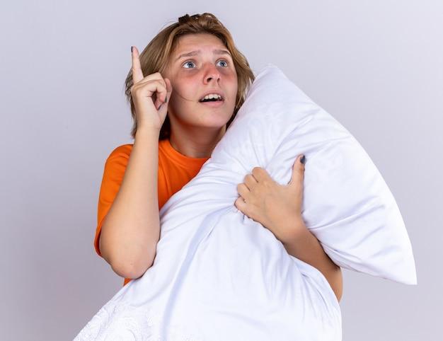 Ongezonde jonge vrouw in oranje t-shirt met kussen die zich ziek voelt en lijdt aan griep die verrast opkijkt en laat zien dat wijsvinger een nieuw idee heeft over de witte muur