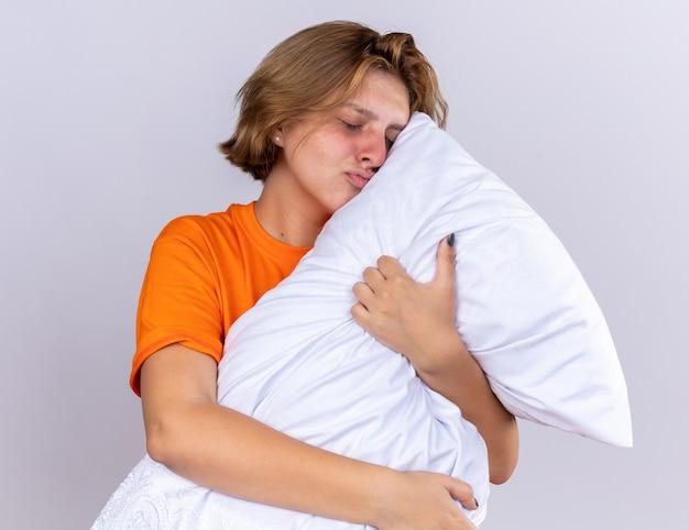 Ongezonde jonge vrouw in oranje t-shirt met kussen die zich ziek voelt lachend met gesloten ogen kussend kussen over witte muur