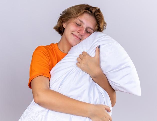 Ongezonde jonge vrouw in oranje t-shirt met kussen glimlachend met gesloten ogen staande over witte muur