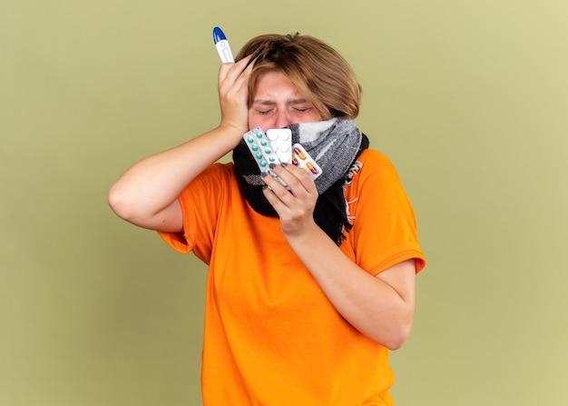 Ongezonde jonge vrouw in oranje t-shirt met warme sjaal om nek en gezicht zich onwel voelen lijden aan koude vasthouden van pillen en thermometer met koorts op zoek bezorgd op groene muur