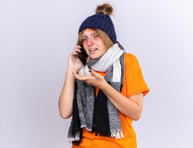 Ongezonde jonge vrouw in oranje t-shirt met warme sjaal om nek en hoed voelt zich verschrikkelijk en lijdt aan griep praten op mobiele telefoon met droevige uitdrukking bezorgd over witte muur