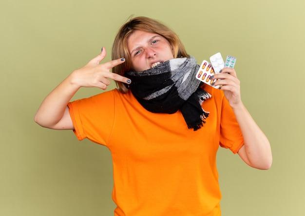 Ongezonde jonge vrouw in oranje t-shirt met warme sjaal om nek voelt zich beter en lijdt aan griep met verschillende pillen die er zelfverzekerd uitzien