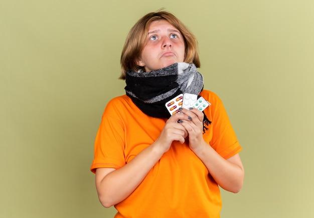 Ongezonde jonge vrouw in oranje t-shirt met warme sjaal om nek voelt zich onwel en lijdt aan griep die verschillende pillen vasthoudt en verward kijkt met droevige uitdrukking die over groene muur staat