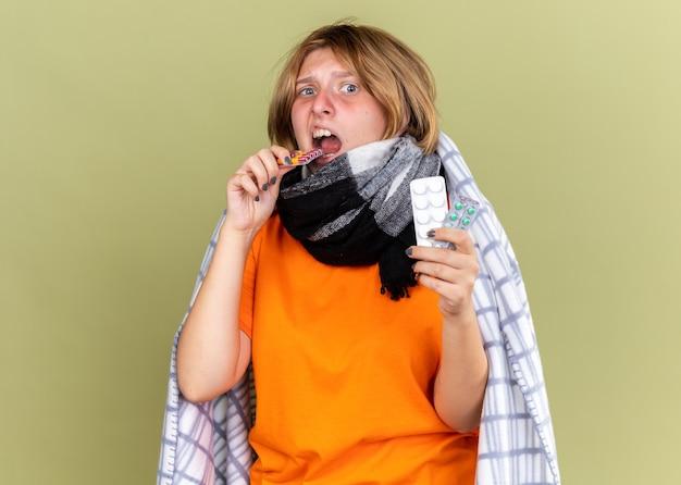 Ongezonde jonge vrouw in oranje t-shirt met warme sjaal om nek voelt zich onwel en lijdt aan griep met verschillende pillen die er verward uitzien