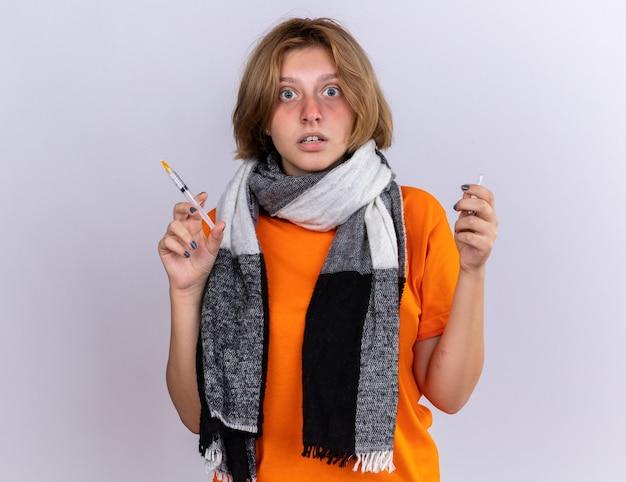 Ongezonde jonge vrouw in oranje t-shirt met warme sjaal voelt zich verschrikkelijk en lijdt aan griep met spuit en ampul verward over witte muur staan