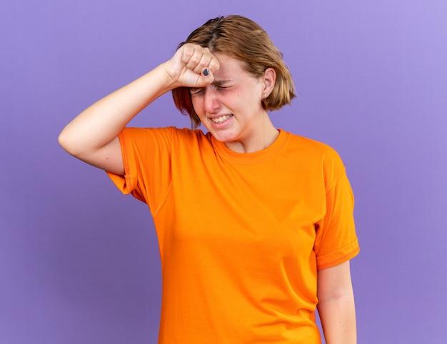 Ongezonde jonge vrouw in oranje t-shirt voelt zich vreselijk als ze haar voorhoofd aanraakt terwijl ze zich duizelig voelt met griep?