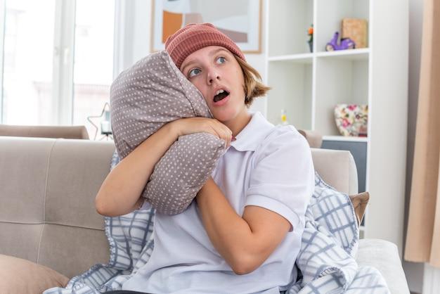 Ongezonde jonge vrouw in warme muts met deken die er onwel en ziek uitziet en lijdt aan verkoudheid en griep met kussen opzij kijkend bezorgd zittend op de bank in een lichte woonkamer