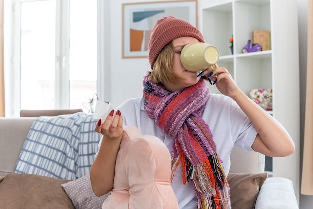 Ongezonde jonge vrouw in warme muts met sjaal die er onwel en ziek uitziet en een kop houdt die hete thee drinkt om beter te worden, lijdend aan verkoudheid en griep zittend op de stoel in een lichte woonkamer