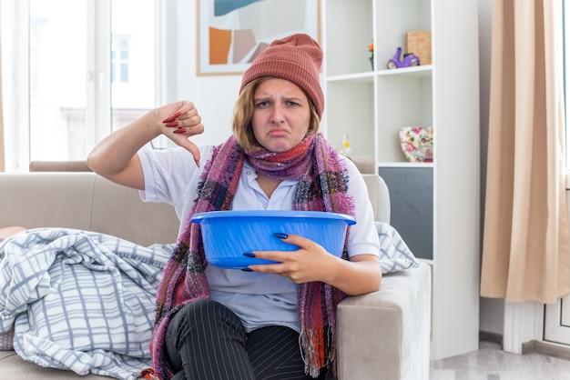 Ongezonde jonge vrouw in warme muts met sjaal om nek met bekken voelt zich misselijk en ziet er onwel en ziek uit met duimen naar beneden zittend op de bank in een lichte woonkamer