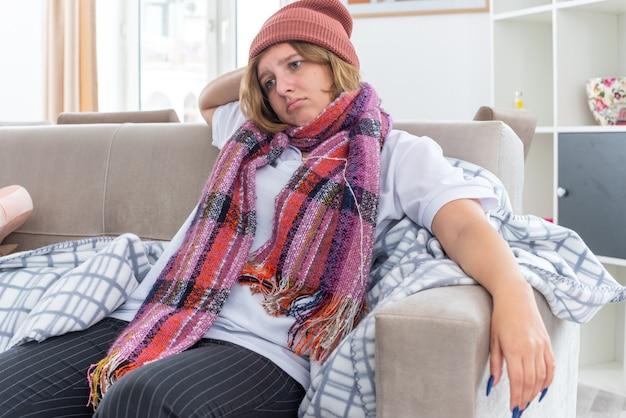 Ongezonde jonge vrouw in warme muts met sjaal om nek voelt zich onwel en ziek die lijdt aan verkoudheid en griep en ziet er bezorgd uit zittend op de bank in een lichte woonkamer
