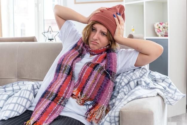 Ongezonde jonge vrouw in warme muts met sjaal om nek zich onwel en ziek voelen die lijdt aan verkoudheid en griep die het hoofd aanraakt met hoofdpijn en koorts zittend op de bank in een lichte woonkamer