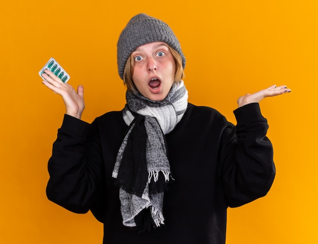 Ongezonde jonge vrouw met een warme muts en een sjaal om haar nek die zich ziek voelt en lijdt aan verkoudheid en griep die pillen vasthoudt en er verbaasd en verward uitziet terwijl ze over de oranje muur staat