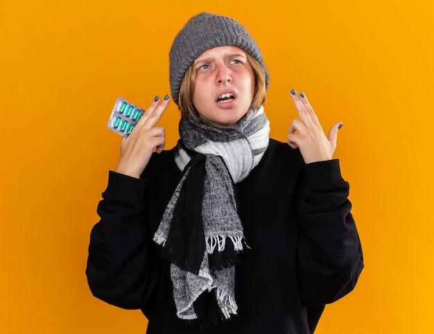 Ongezonde jonge vrouw met een warme muts en een sjaal om haar nek die zich ziek voelt en lijdt aan verkoudheid en griep terwijl ze pillen vasthoudt en verward opkijkt